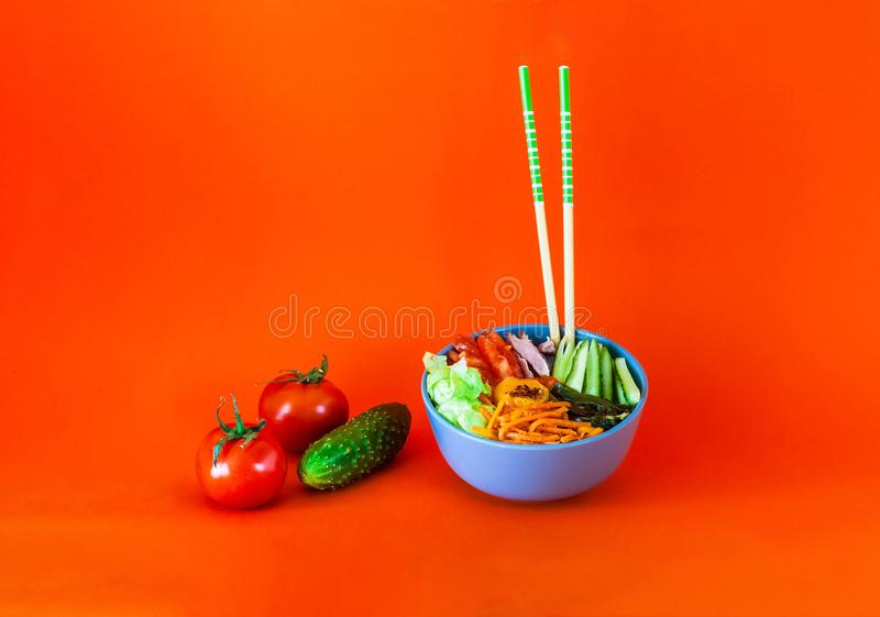 Traditional dish of Korean cuisine. Bibimbap with beef, vegetables and egg on coral background. Top view. stock photography