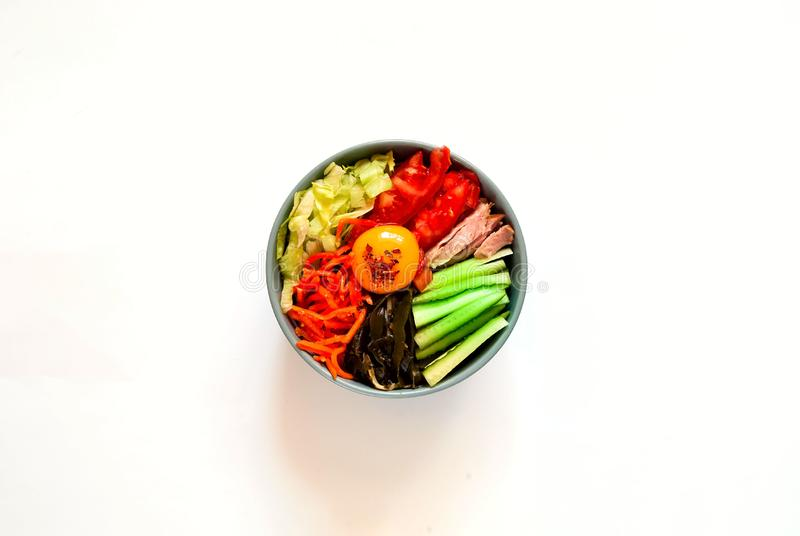 Traditional dish of Korean cuisine. Bibimbap with beef, vegetables and egg on white isolated background. royalty free stock images