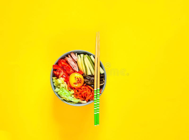 Traditional dish of Korean cuisine. Bibimbap with beef, vegetables and egg on yellow background. stock images