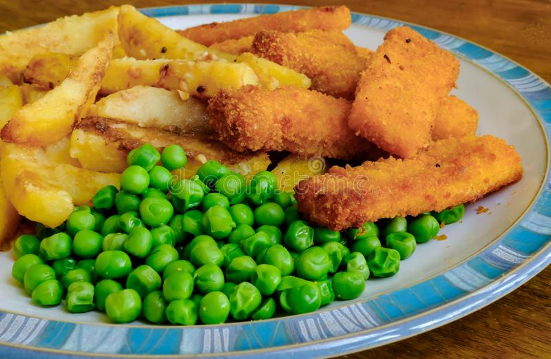 Freshly cooked fish fingers, potato chips and garden peas on a plate. stock image