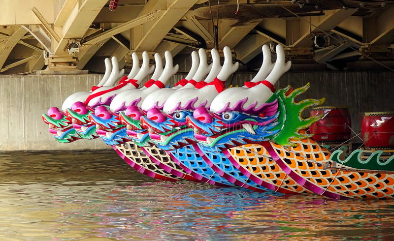Traditional Dragon Boats in Taiwan. KAOHSIUNG, TAIWAN -- MAY 21, 2017: Traditional dragon boats are anchored under a bridge on the Love River in preparation for stock photos