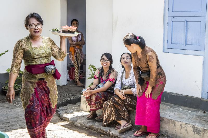 Traditional dressed Balinese woman serving food for family stock image