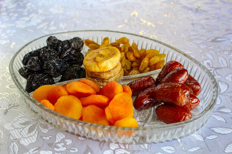Traditional dried fruits in a glass tray. Jewish holiday Tu Bishvat, Israel. Traditional dried fruits in a glass tray: Apricots, Dates, Raisins, Prunes, Figs stock photography