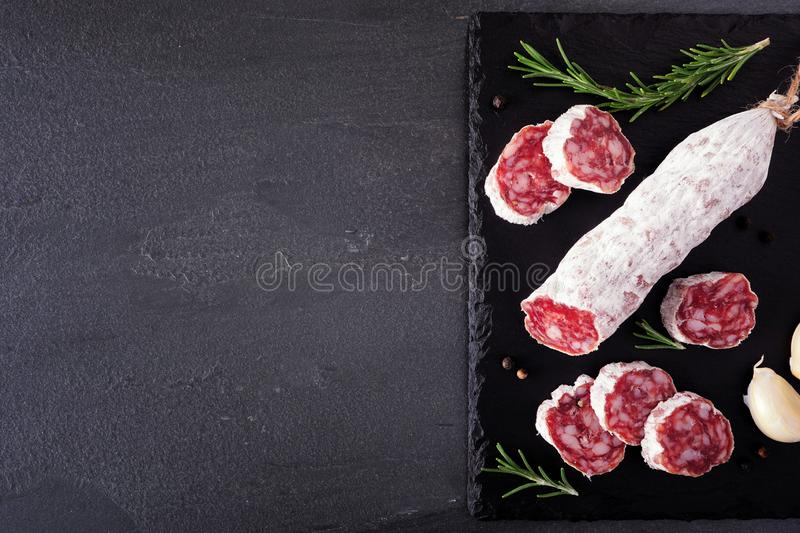 Traditional dry cured sausage, top view, sliced on a slate platter with copy space stock photography