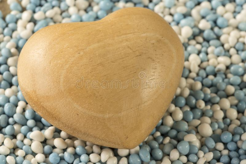 Traditional Dutch food aniseed balls, muisjes, for birth of a son-3. Wooden heart with space for text, in heap blue and white aniseed balls called `muisjes` stock photos