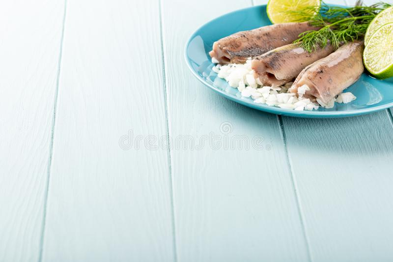 Traditional dutch food herring fish. Freshly salted herring fish, traditional dutch delicacy called hollandse nieuwe on turquoise plate and wooden background stock photo