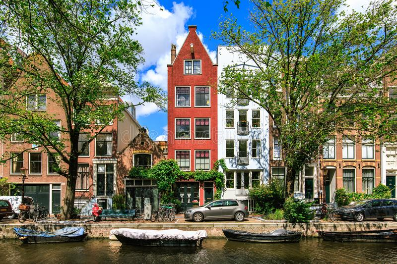 Traditional dutch houses and boats on canal in the most romantic city. Tranquil scene of Amsterdam street in summer. Netherlands. stock photos
