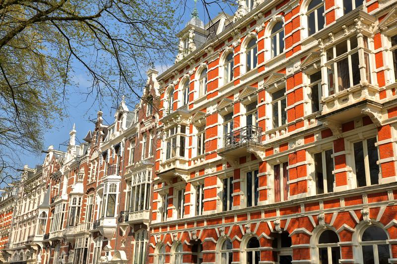 Traditional dutch old facades located on Weesperzijde Street along Amstel river, Amsterdam royalty free stock images