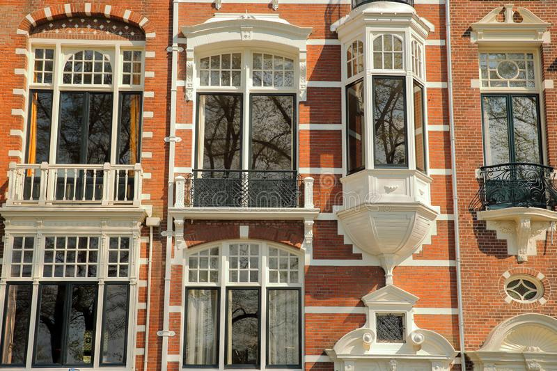 Traditional dutch old facades located on Weesperzijde Street along Amstel river, Amsterdam royalty free stock photography