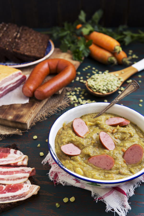 Traditional Dutch pea soup and ingredients on a rustic table stock photo