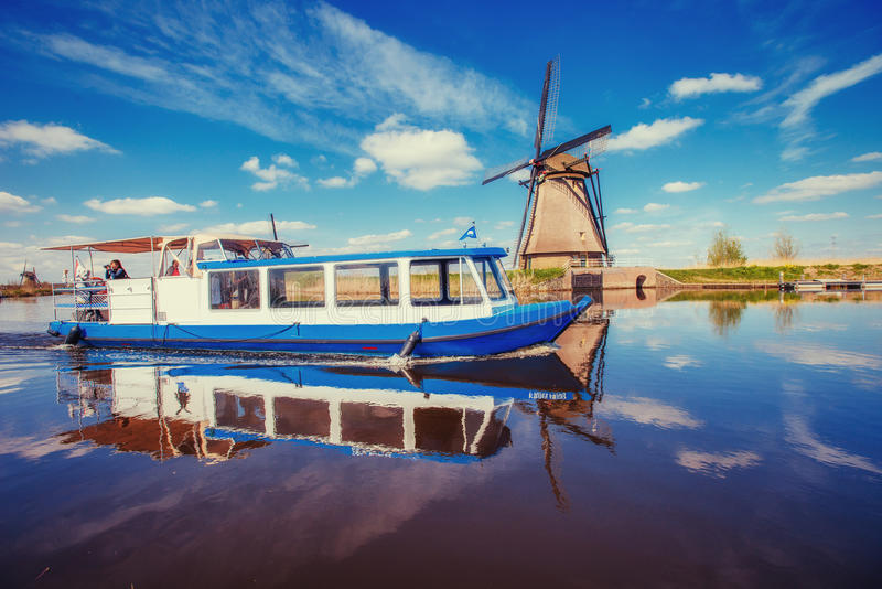 Traditional Dutch windmills from the channel Rotterdam. Boat tha. T floats on the river. Sunny spring day. Holland stock photo