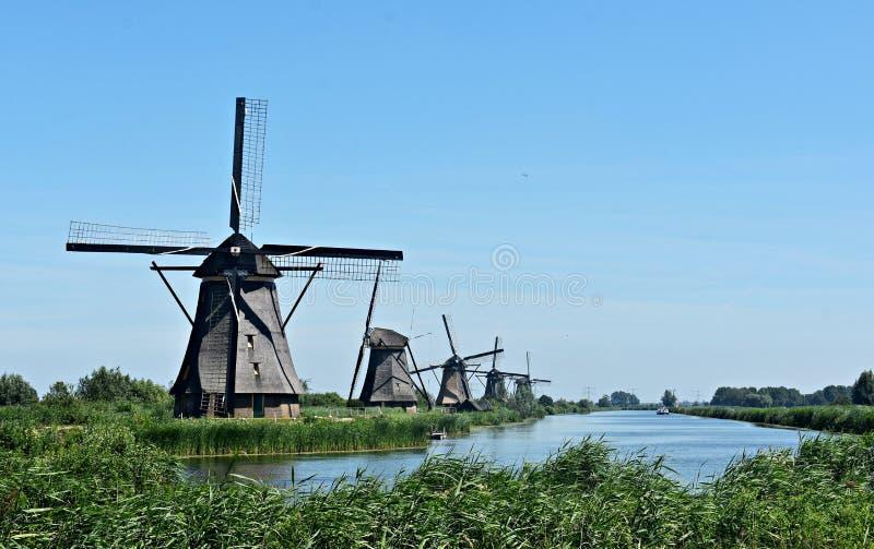 Traditional Dutch windmills at Kinderdijk, Holland. Beautiful landscape with green grass and traditional Dutch windmills on the shore of a river in Kinderdijk stock images