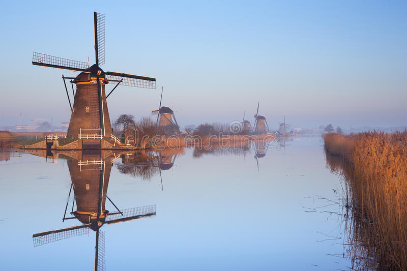 Traditional Dutch windmills at sunrise at the Kinderdijk. Traditional Dutch windmills reflected in perfectly still water on a cold morning in winter, at the stock image