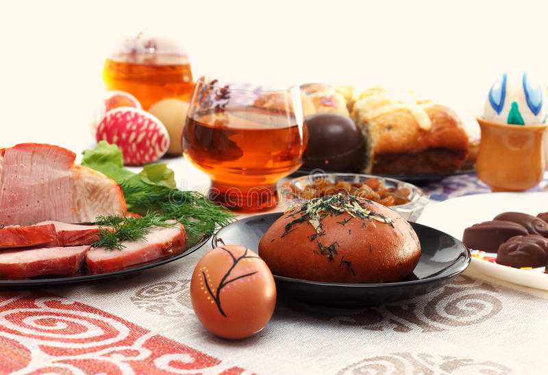 Traditional easter dinner set with sliced meat, bread with herbs, handmade colored eggs, chocolates, easter cake and glasses of ju. Ice on colorful tablecloth royalty free stock images