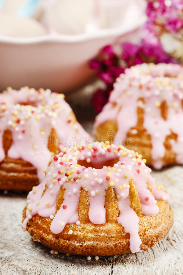 Traditional easter yeast cake. Covered with pink icing and colorful sprinkles royalty free stock images