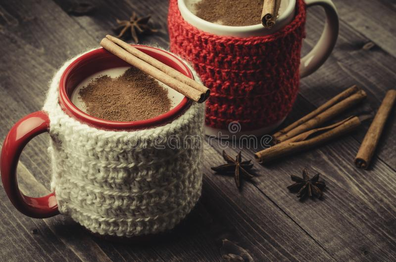 traditional eggnog in red and white mugs with cinnamon/traditional eggnog in red and white mugs with cinnamon on a dark background stock photo