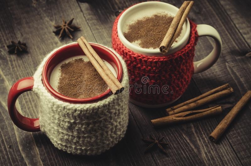 traditional eggnog in red and white mugs with cinnamon/traditional eggnog in red and white mugs with cinnamon on a dark stock images