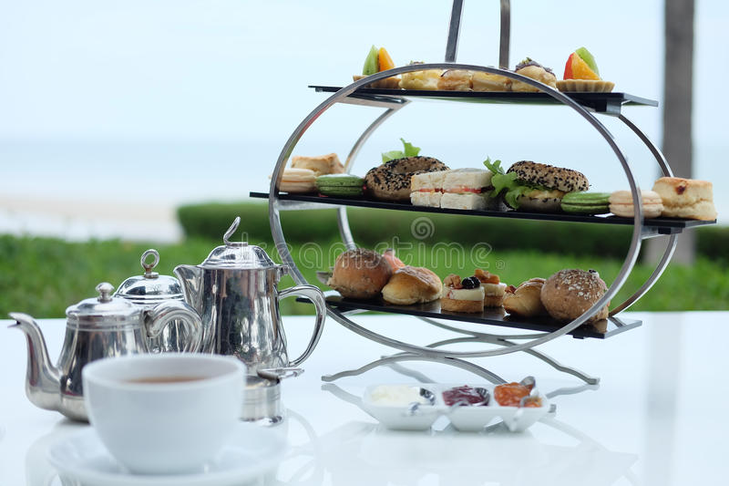 Traditional english afternoon tea. With cakes ,sandwiches ,macaron , jelly, jam, and scones royalty free stock image
