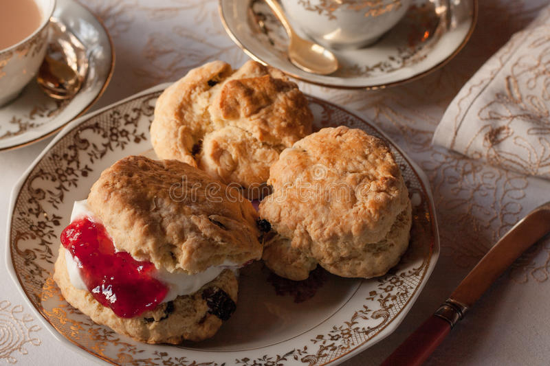 Traditional English Afternoon Tea and Scones. A traditional english afternoon tea of scones with clotted cream and strawberry jam on an elegant plate and cloth stock photos
