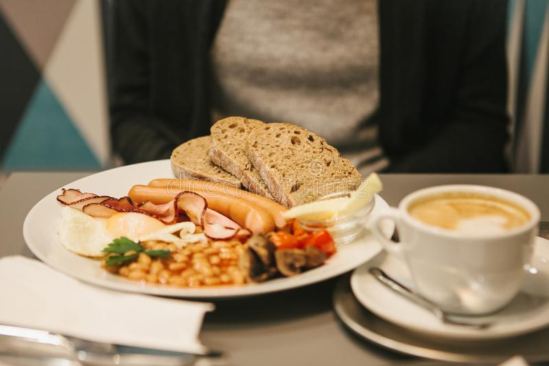 Traditional English breakfast. A cup of coffee with cappuccino is next to it. National food. A famous dish all over the. Traditional English breakfast. A cup of stock photography