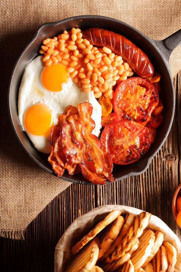 Traditional english breakfast food with eggs sausages bacon bean. S and toasts, close up top view royalty free stock photography
