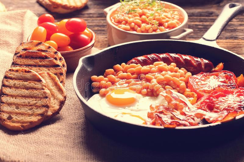 Traditional english breakfast food with eggs sausages bacon bean. S and toasts, close up vintage view stock images