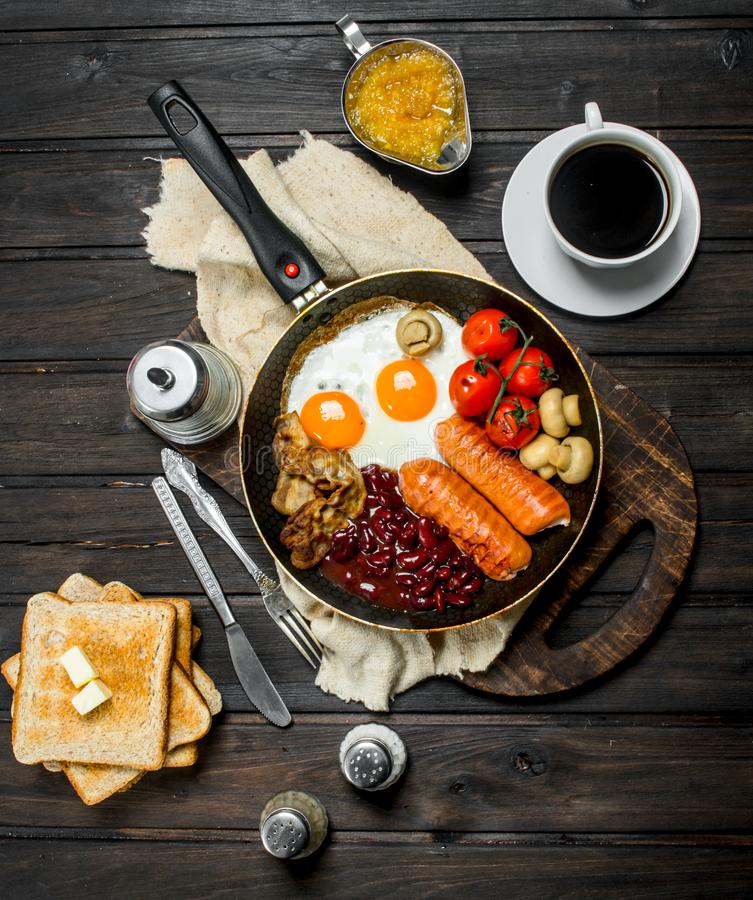 Traditional English Breakfast with a variety of food and aromatic coffee. On a wooden background royalty free stock photo