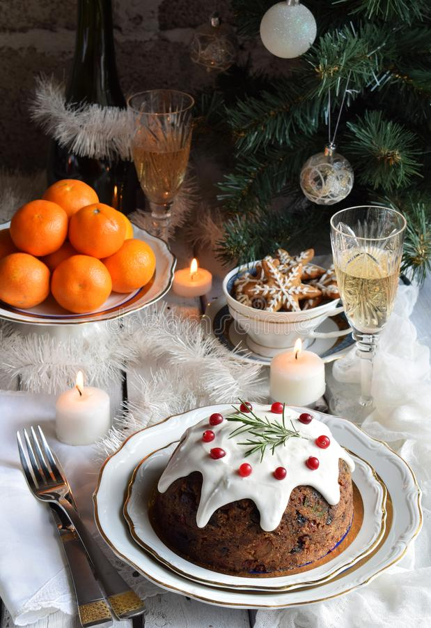Traditional english Christmas steamed pudding with winter berries, dried fruits, nut in festive setting with Xmas tree, burning ca stock image