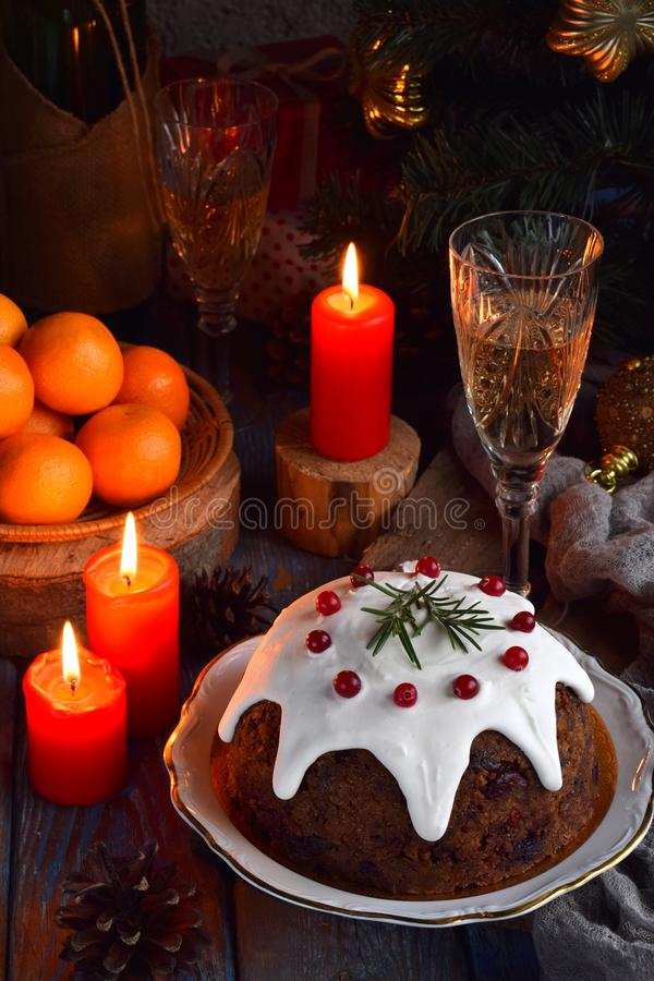 Traditional english Christmas steamed pudding with winter berries, dried fruits, nut in festive setting with Xmas tree, burning ca royalty free stock photography