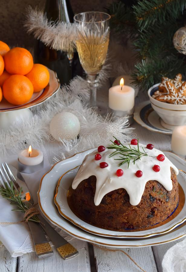 Traditional english Christmas steamed pudding with winter berries, dried fruits, nut in festive setting with Xmas tree, burning ca royalty free stock image