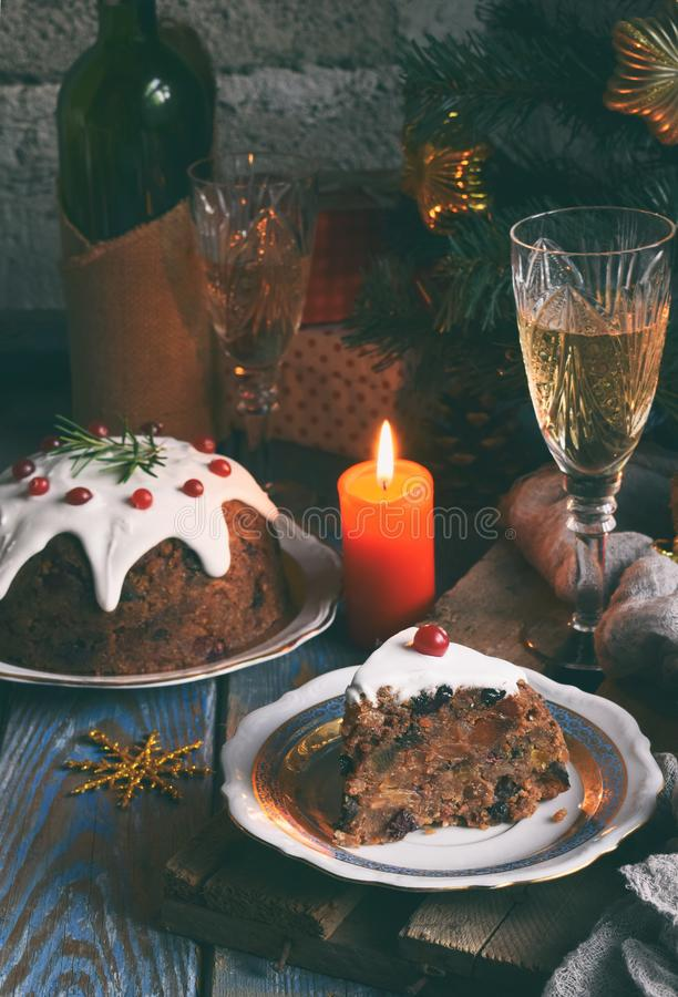 Traditional english Christmas steamed pudding with winter berries, dried fruits, nut in festive setting with Xmas tree and burning stock images