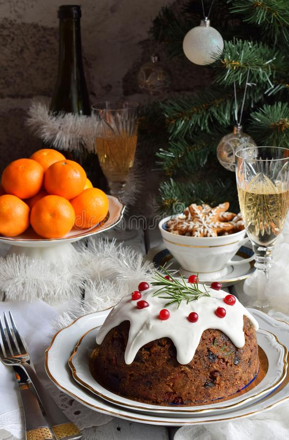 Traditional english Christmas steamed pudding with winter berries, dried fruits, nut in festive setting with Xmas tree and burning royalty free stock image