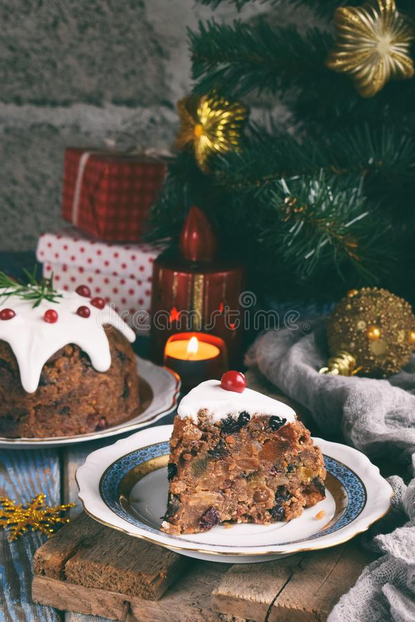 Traditional english Christmas steamed pudding with winter berries, dried fruits, nut in festive setting with Xmas tree and burning. Candle. Fruit cake royalty free stock photos