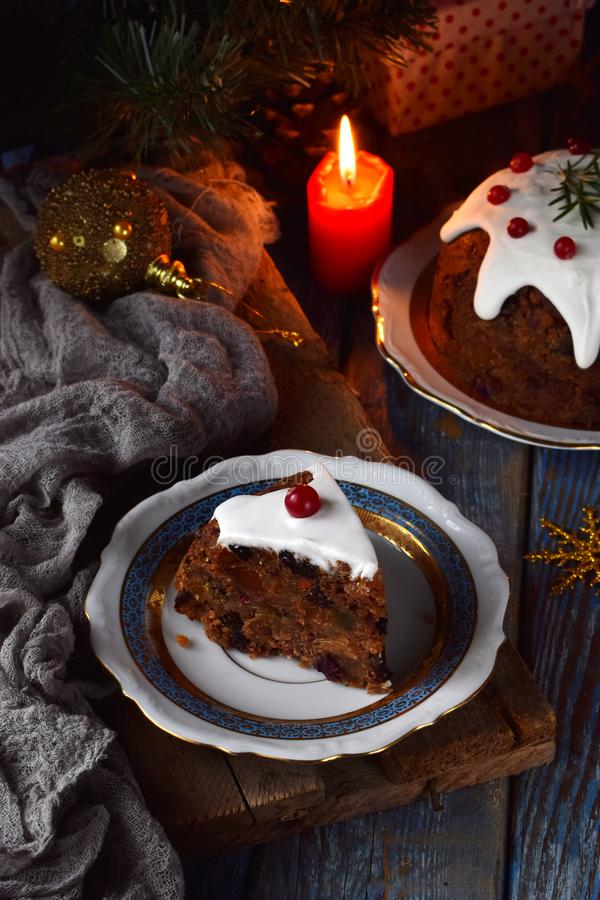 Traditional english Christmas steamed pudding with winter berries, dried fruits, nut in festive setting with Xmas tree and burning stock photos