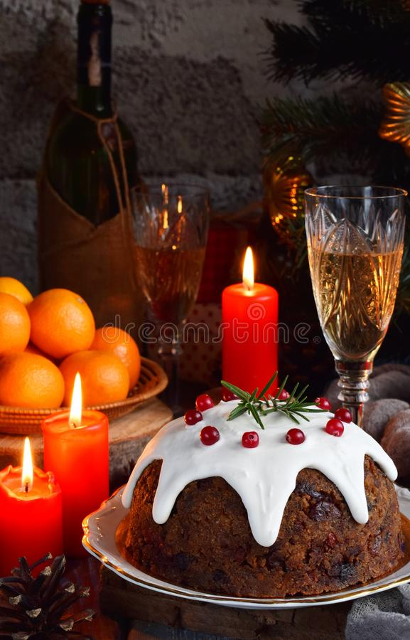 Traditional english Christmas steamed pudding with winter berries, dried fruits, nut in festive setting with Xmas tree and burning royalty free stock photography