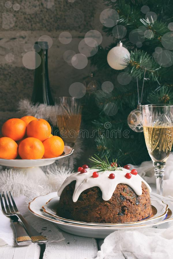 Traditional english Christmas steamed pudding with winter berries, dried fruits, nut in festive setting with Xmas tree, tangerines stock photo