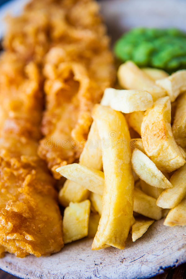 Traditional english food - Fish and chips with mushy peas. On an old metal plate stock photos