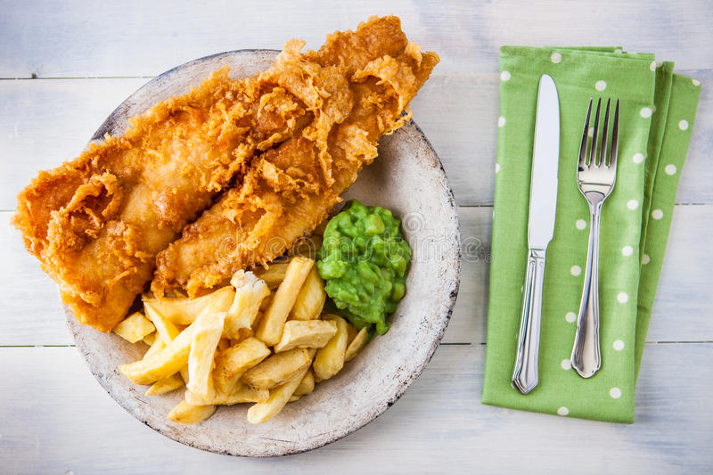 Traditional english food - Fish and chips with mushy peas. On a white wooden background royalty free stock photos