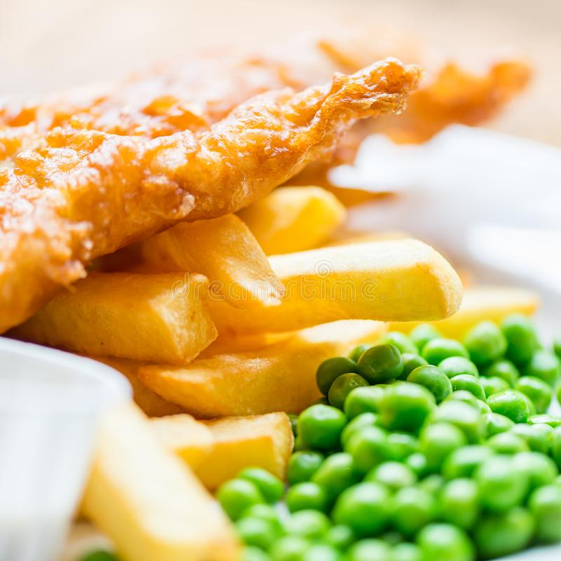 Traditional English Food such as Fish and Chips. With green peas served in the Pub or Restaurant royalty free stock photography