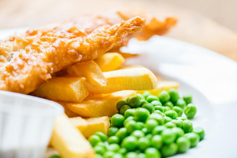 Traditional English Food such as Fish and Chips. With green peas served in the Pub or Restaurant stock photos