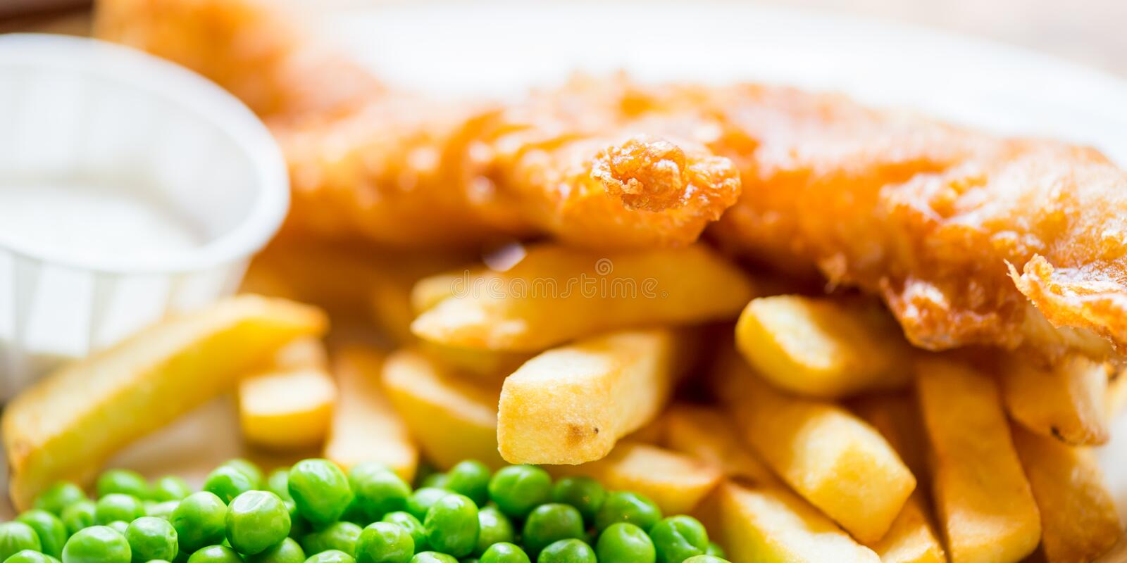 Traditional English Food such as Fish and Chips. With green peas served in the Pub or Restaurant stock image