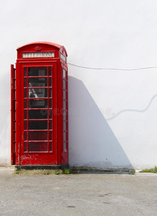 Traditional english phone box on a street in england. In the sunshine with good lighting royalty free stock photography