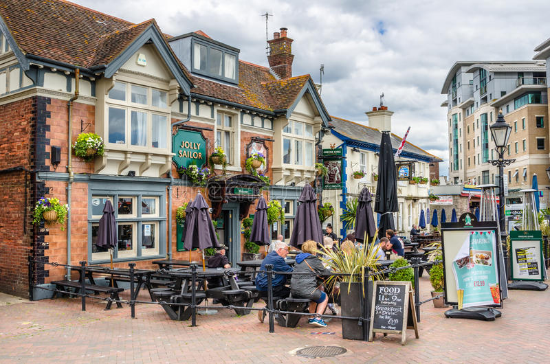 Traditional English Pub with People having Lunch Outdoor. Exterior of a Traditional English Pub in Poole, Dorset, UK royalty free stock images