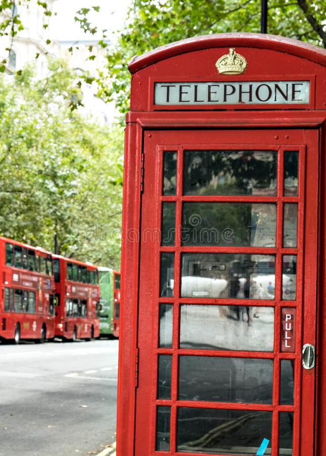 Traditional English Red Telephone Phone Box and Red Double Decker Buses London England. English K6 Telephone Phone Box with pre 1955 Tudor Crown emblazoned at royalty free stock image