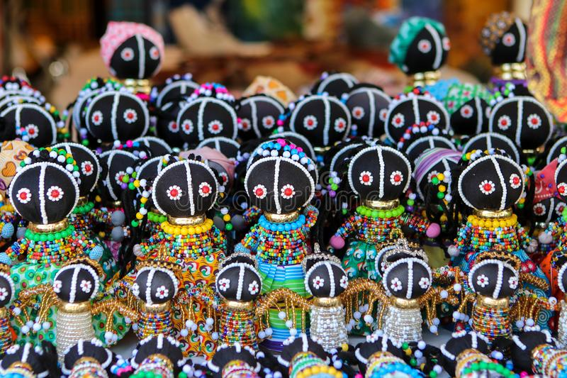 Traditional ethnic African handmade dolls with multicolored bead decoration at local market in Cape Town, South Africa. Souvenirs from Africa stock images
