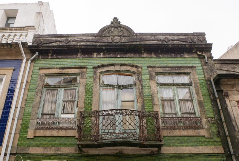 Traditional facade of old Portuguese architecture house with green tiles and metal balcony. Weathered, broken windows. royalty free stock photography