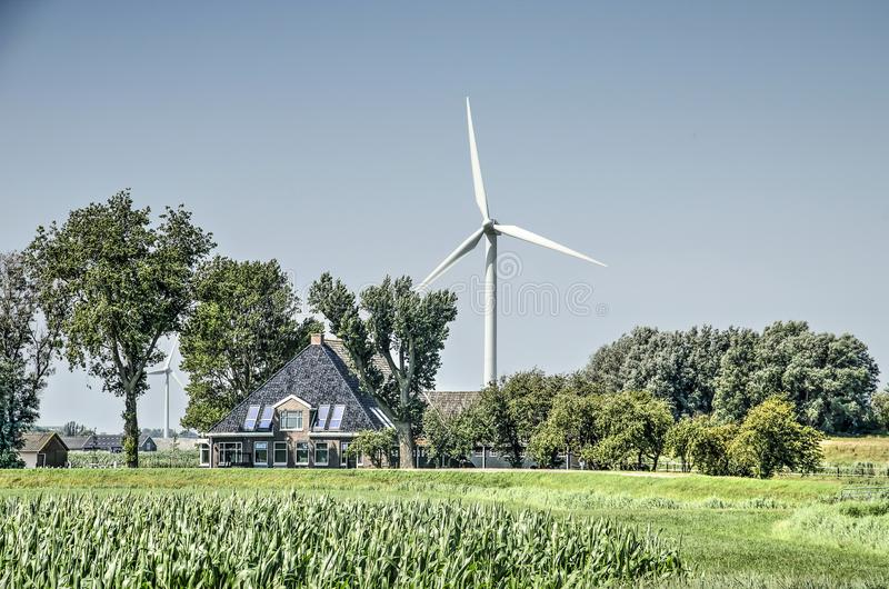 Traditional farmhouse, modern wind turbine royalty free stock image