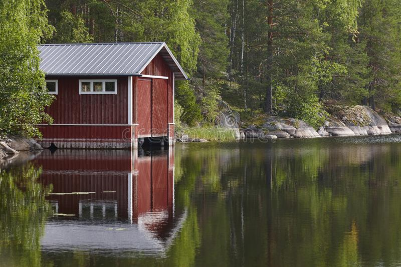 Traditional Finland landscape with lake, forest and red wooden h royalty free stock image
