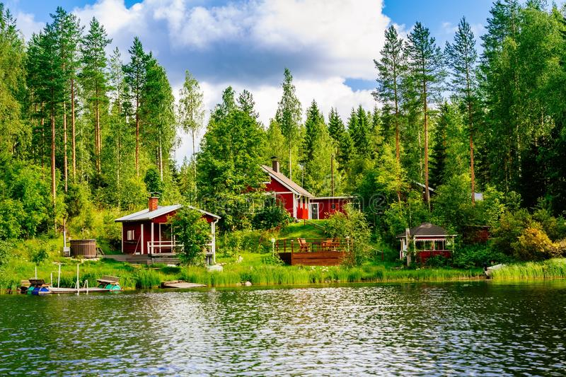 A traditional Finnish wooden cottage with a sauna and a barn on the lake shore. Summer rural Finland. stock photo