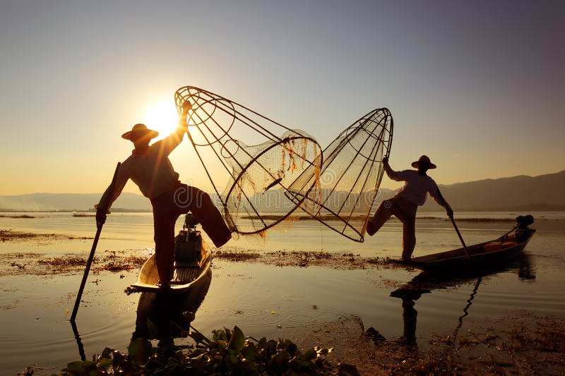 Traditional fishermen silhouette at Inle lake. Myanmar travel attraction landmark - Traditional Burmese fishermen with fishing net at Inle lake in Myanmar famous royalty free stock images